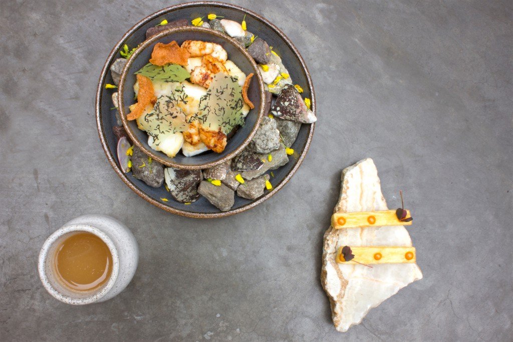 A meal is presented in a dish surrounded with a decoration of stones and flowers that provide context to the food's origin at Central Restaurant, Lima, Peru