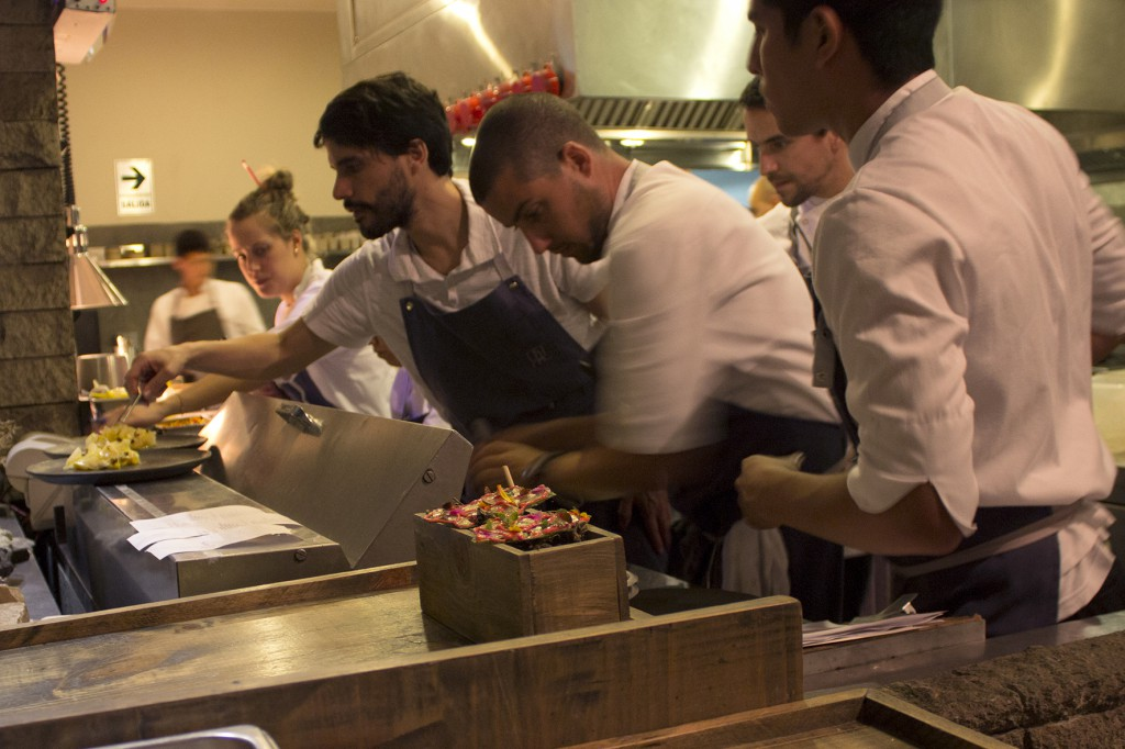 Virgilio in a group of chefs plating a dish in Central's kitchen