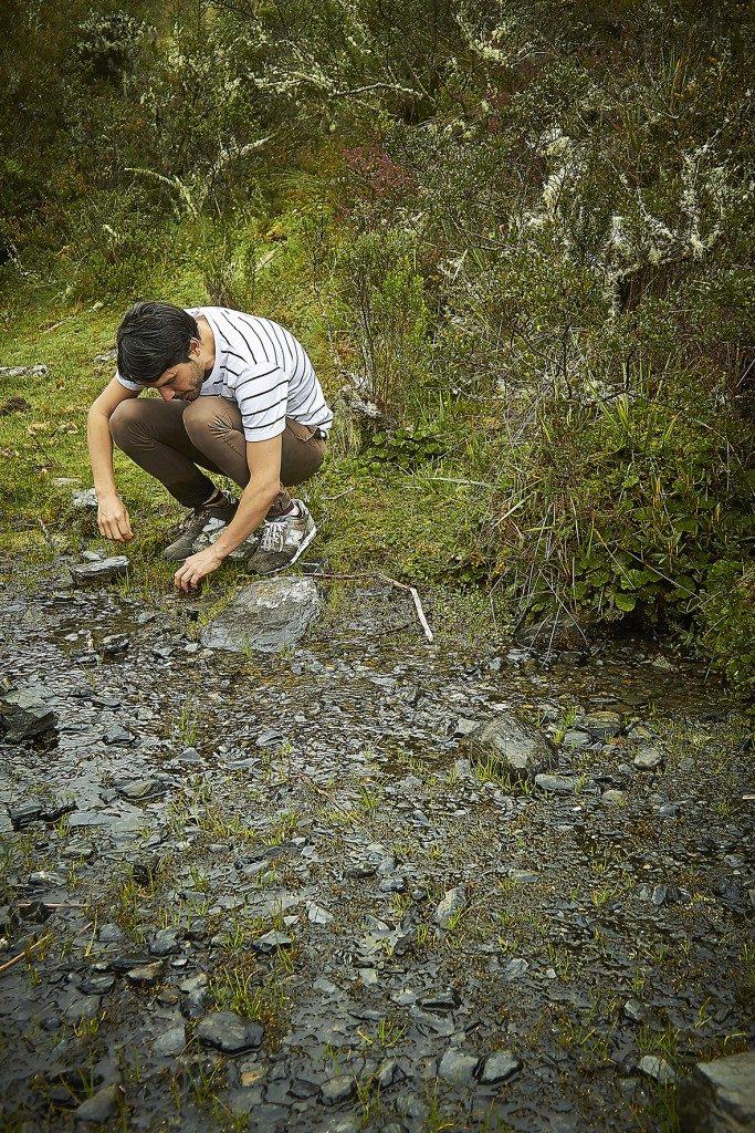 Virgilio Martinez squatting by a shallow, stony rivulet foraging for edible clay, etc, Peru
