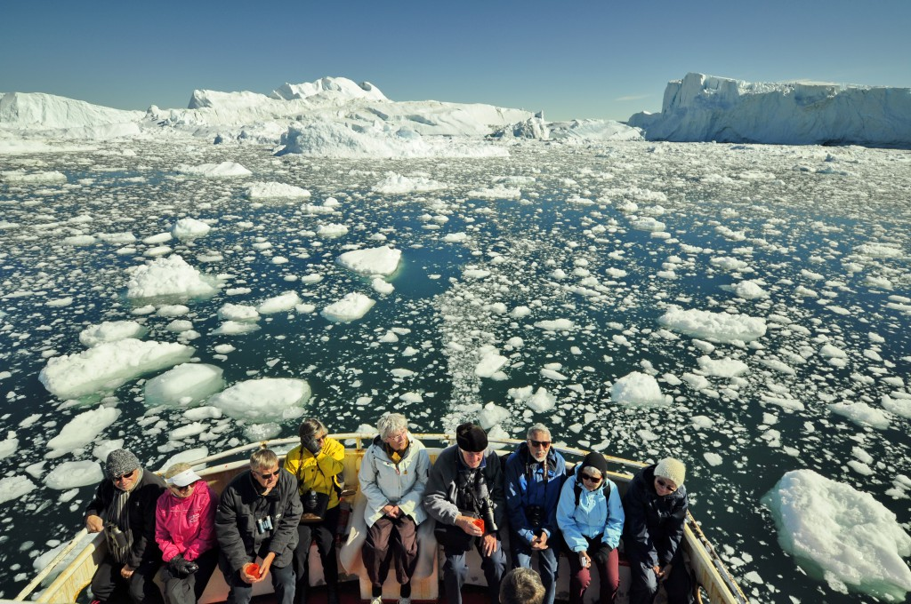 Group on a boat in a sea littered with ice chunks and floes