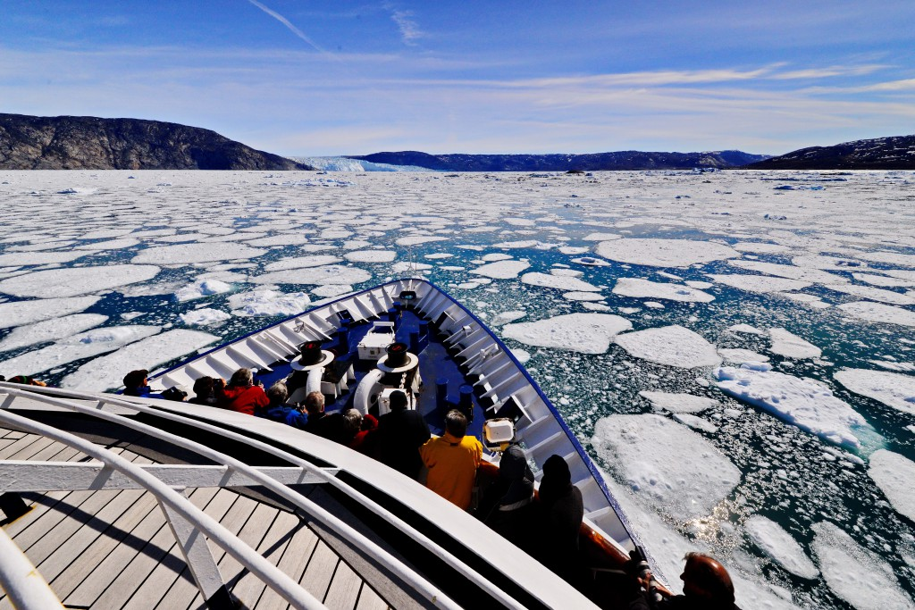 Group at the prow of the Sea Explorer sailing into a sea filled with blocks and chunks of ice, Greenland
