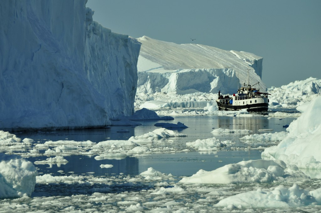 A boat navigating through massive and very tall ice floes through a sea littered with icy