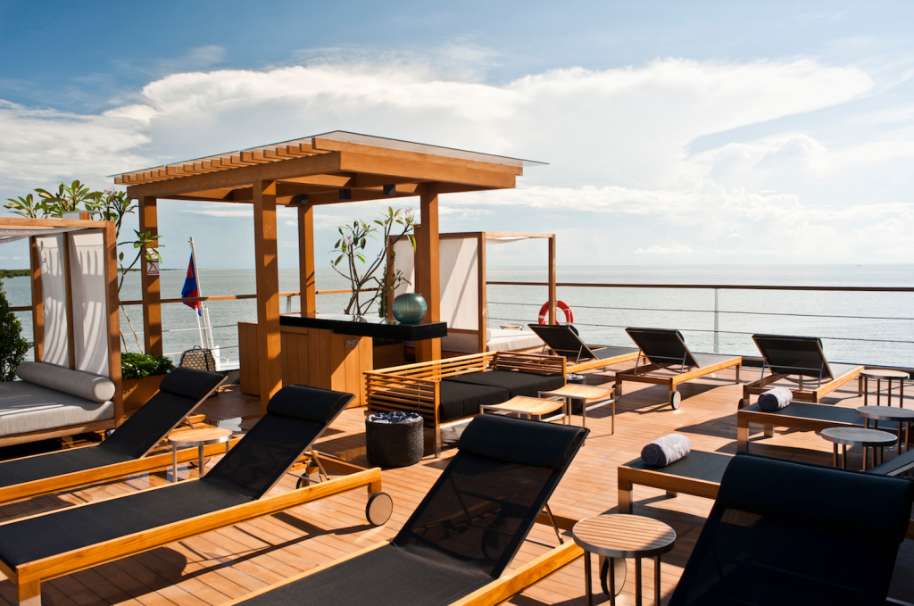 The sun deck of the cruiser with loungers and shaded divans facing out onto the Mekong River, Cambodia
