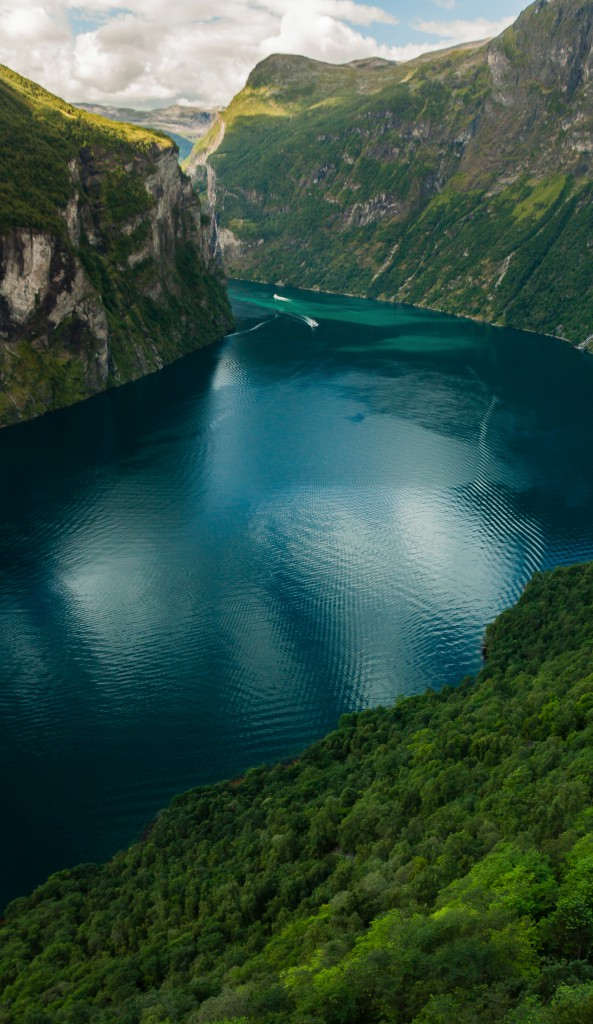 An aerial view into the exceptionally beautiful Geiranger fjord, Norway; looking down and through lush green hills at the flat blue water