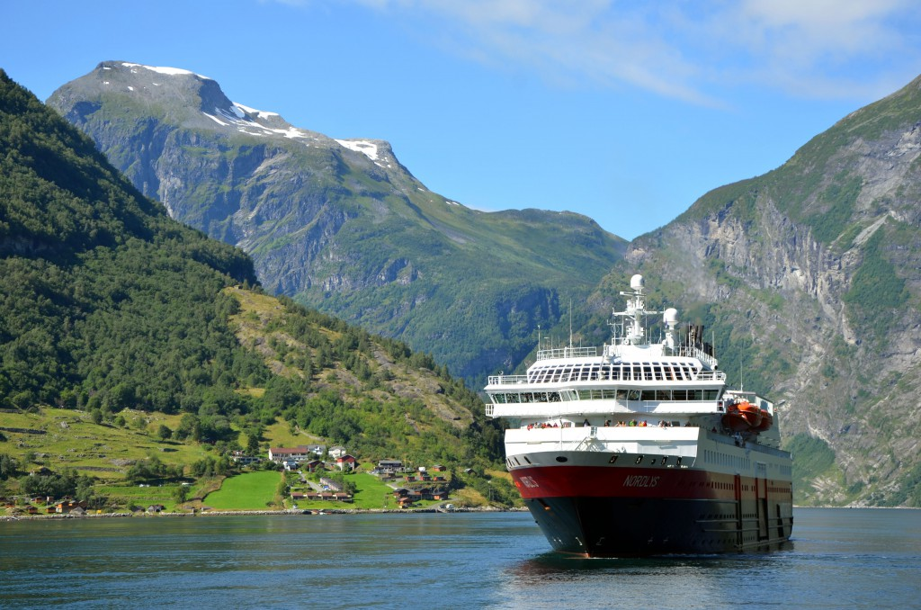 The MS Nordlys, a Norweigian cruise ferry sailing on the fjord with hills in the background