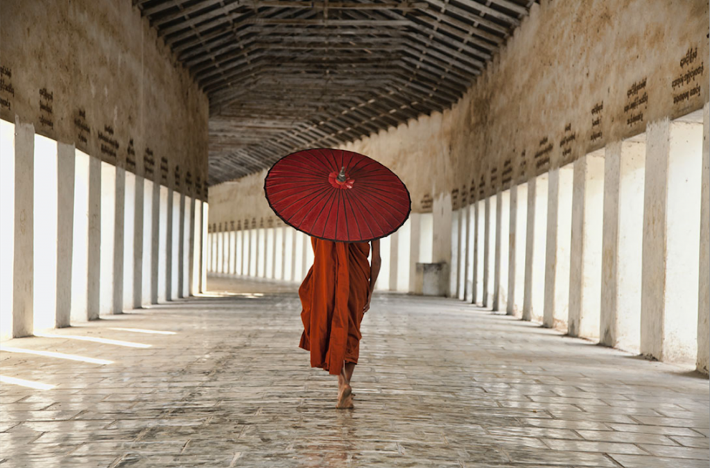 A monk dressed in red robes carrying a red umbrella walking away through a long white covered corridor with pillars on both sides in Myanmar
