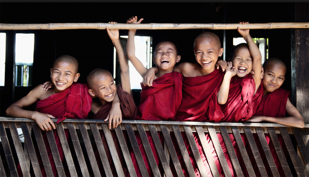 A line of six laughing boys dressed in red robes holding on to a wooden balcony railing