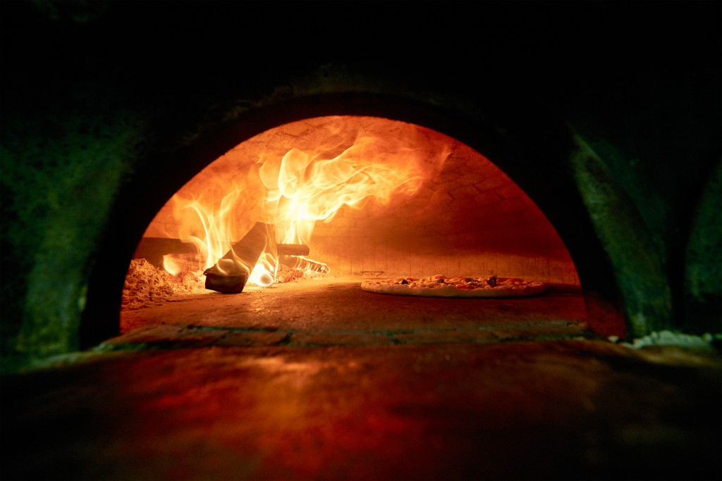 Looking in through a semi-circular opening at a pizza cooking in a blazing oven, Naples