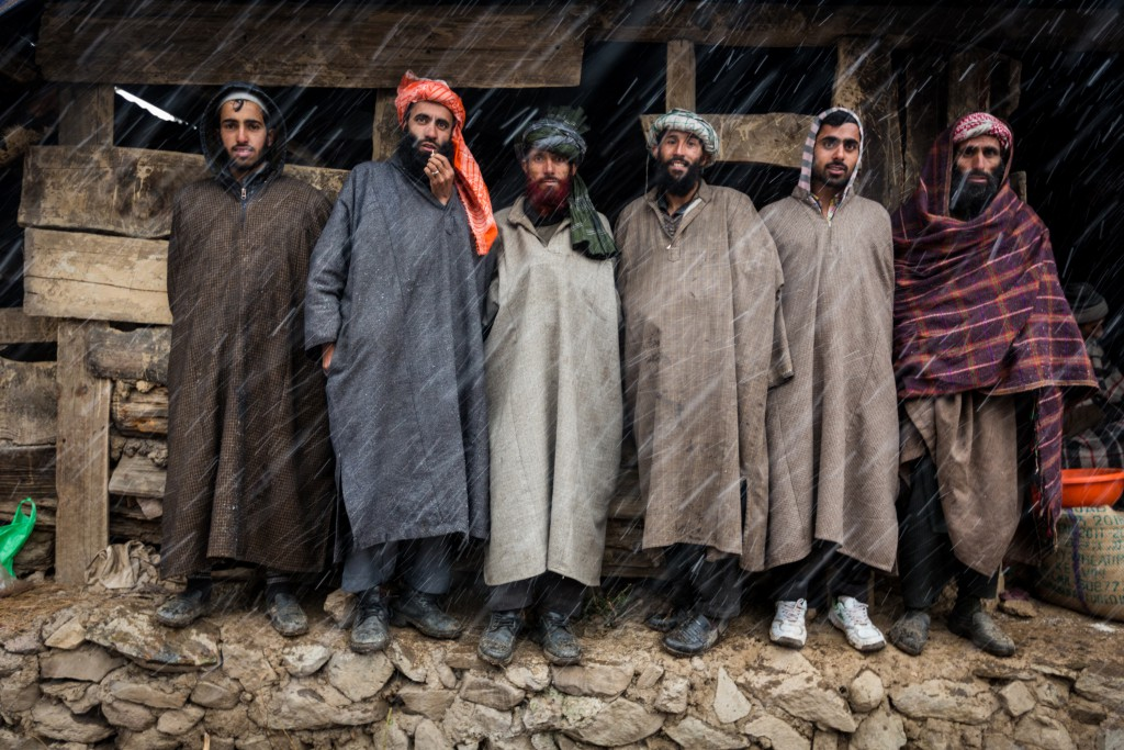 "Six Pahari Gujjar men take refuge from the snow under the eves of a barn. These men wear the Kashmiri, ""pheran"" or woolen poncho to stay warm. Pahalgam, Kashmir, India."