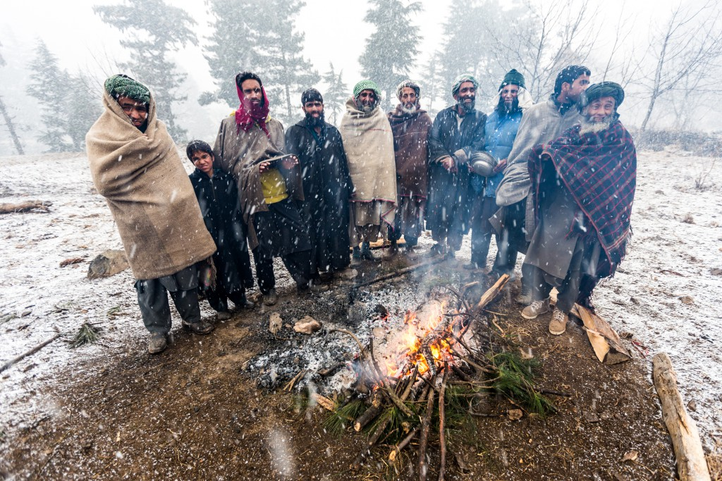 These Gujjars stay close to the fire to stay warm during preparations for a wedding meal. Pahalgam, Kashmir, India.