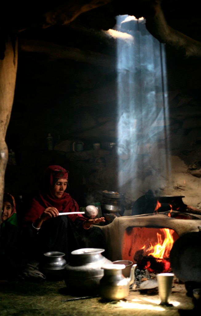 At 3,900 metres a Gujjar woman makes salt tea in her hut on the slopes of Mt. Kolhoi. A shaft of light beams down through the smoke from the vent in her sod roof. Kolahoi, Kashmir, India.