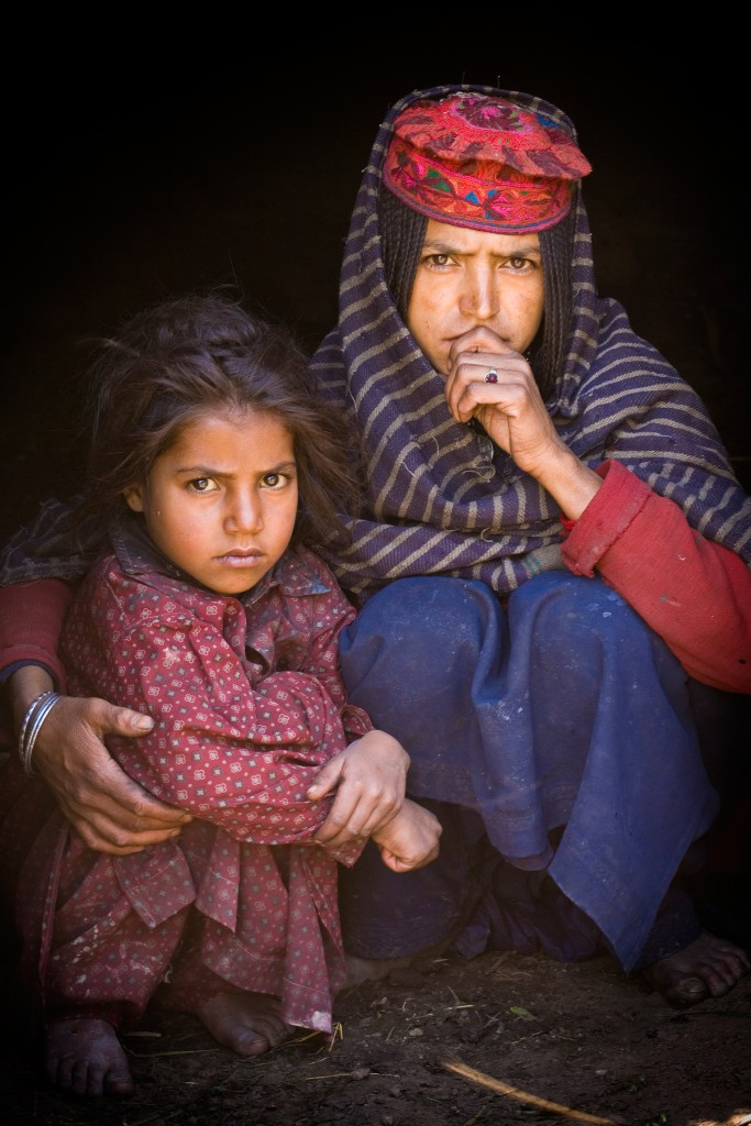 A Bakarwal, Gujjar mother and child sit together in their hut. Note the distinct hat and plaits on the mother. Lidderwat, Kashmir, India.