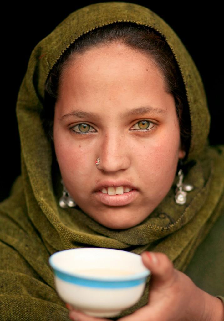 Green eyed Gujjar girl with a cup of salt tea. Lidderwat, Kashmir, India.