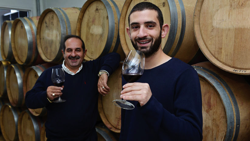 Two brothers holding red wine in goblets standing by wine barrels