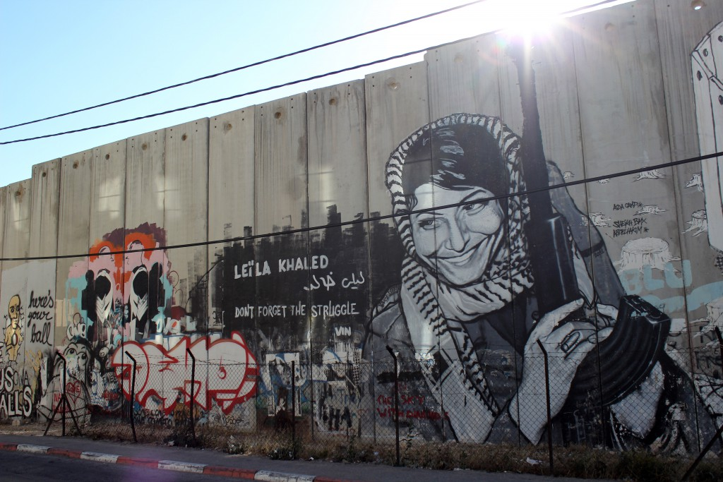 Graffiti including a painting of a smiling Leila Khaled holding a gun on the Israeli separation wall