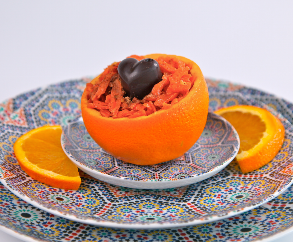 Moroccan carrot salad and a heart shaped raw orange chocolate served in a scooped out orange rind on a plate with two orange slices on either side