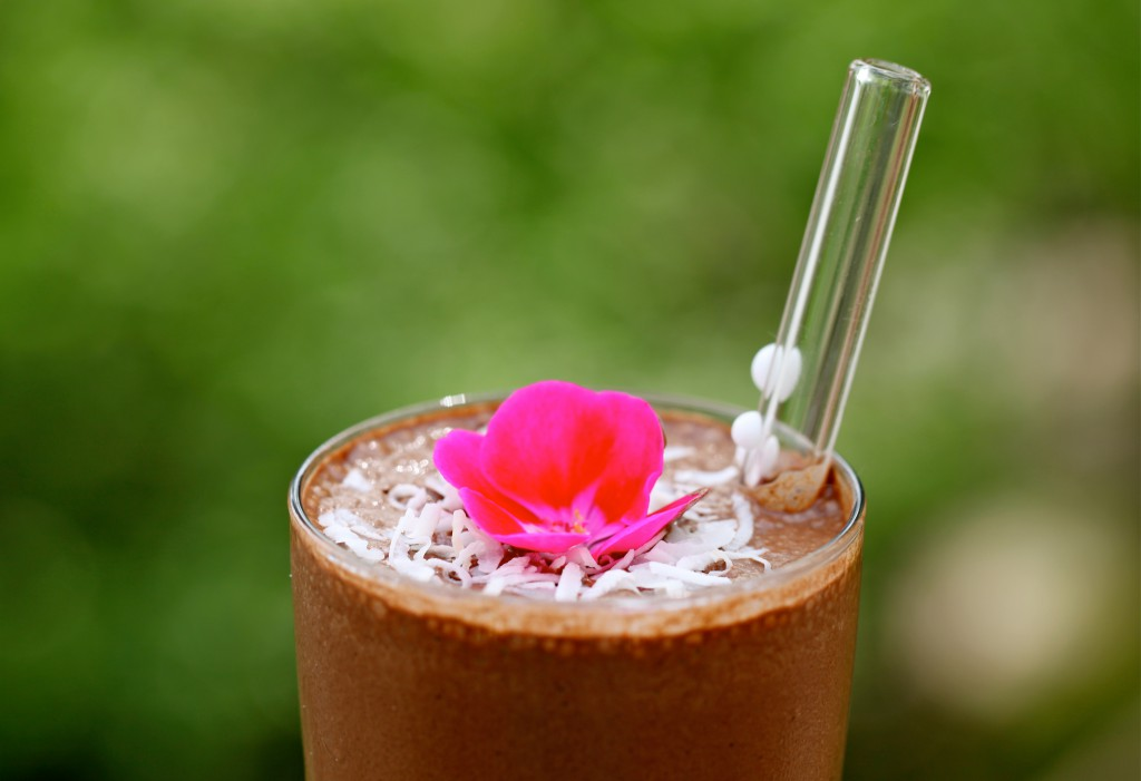 A Jamaican Mocha Teeccino topped with shredded coconut and a red flower in a glass with a clear straw