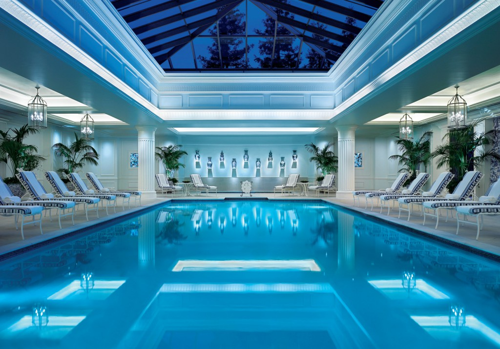 View of a blue pool with loungers around it and a glass roof California Health and Longevity Institute Wellness Retreat