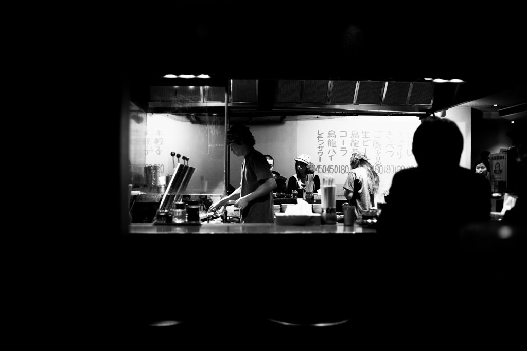 Admiriring the cook's technique while waiting for seats at a neighborhood ramen stall. Photo by Saret Son