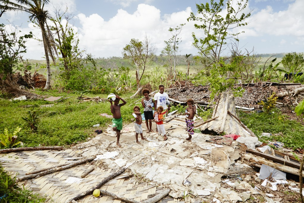 A family stand on their cyclone-flattened home, Vanuatu. Photo by Matt Crawford