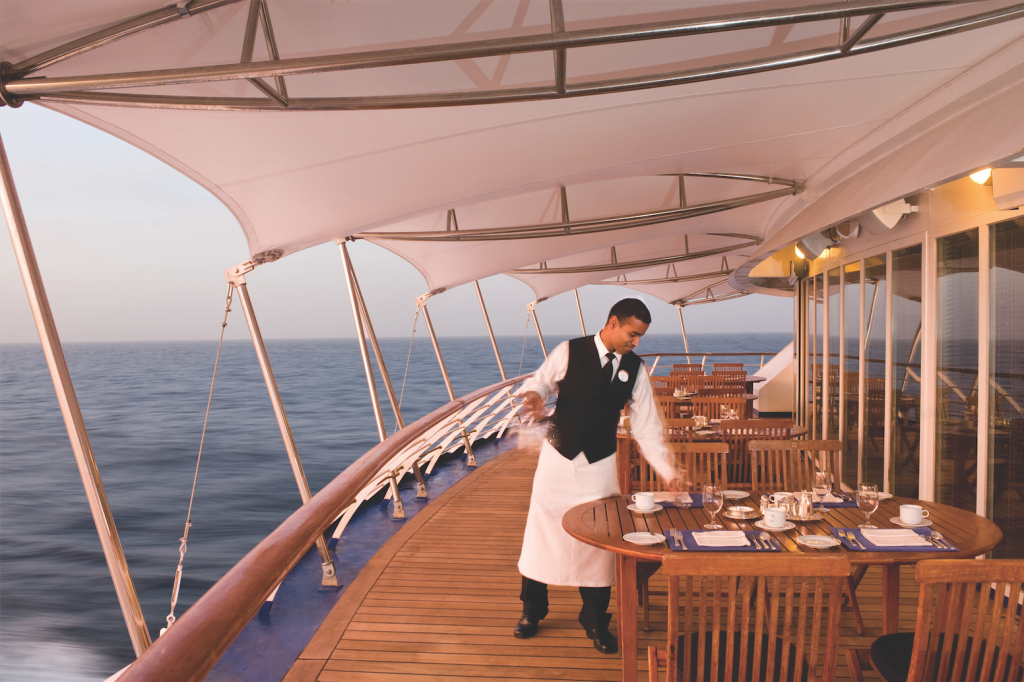 Waiter laying a table on the deck of the Silver Wind