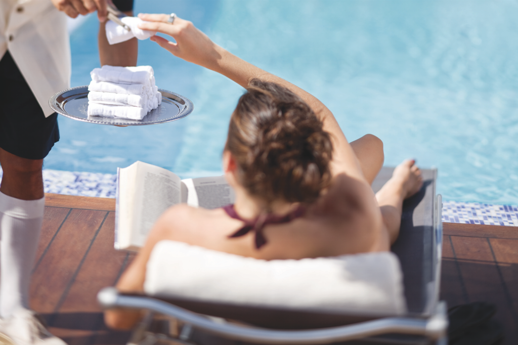 Cold towels being served to a lady reclining by the pool