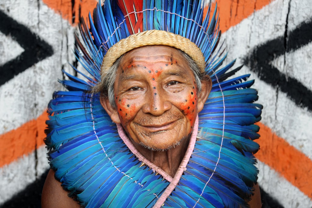 The chief of a village situated near the Amazon River. He wears traditional face paint, a full feather head dress, and his smile shows the warmth and happiness of the peaceful Desana tribe.