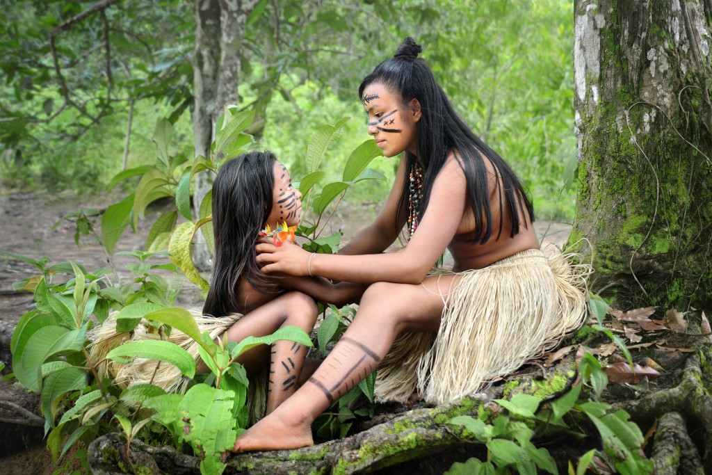 Two girls from the Amazonian Brazilian Desana tribe adjust the necklace and ornaments worn as part of their traditional dress.
