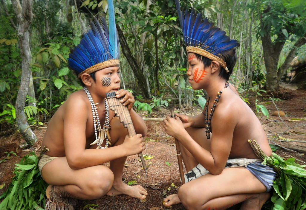 Two Brazilian Amazonian children who live by a river in a traditional tribal community play music together. The feathers in the boys' headdresses are made from a macaw bird, and these are worn to mark the identities of tribal groups.