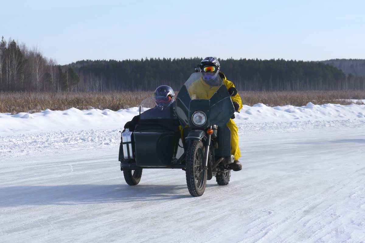 Two people on a bike with sidecar racing through the snow at Lake Baikal
