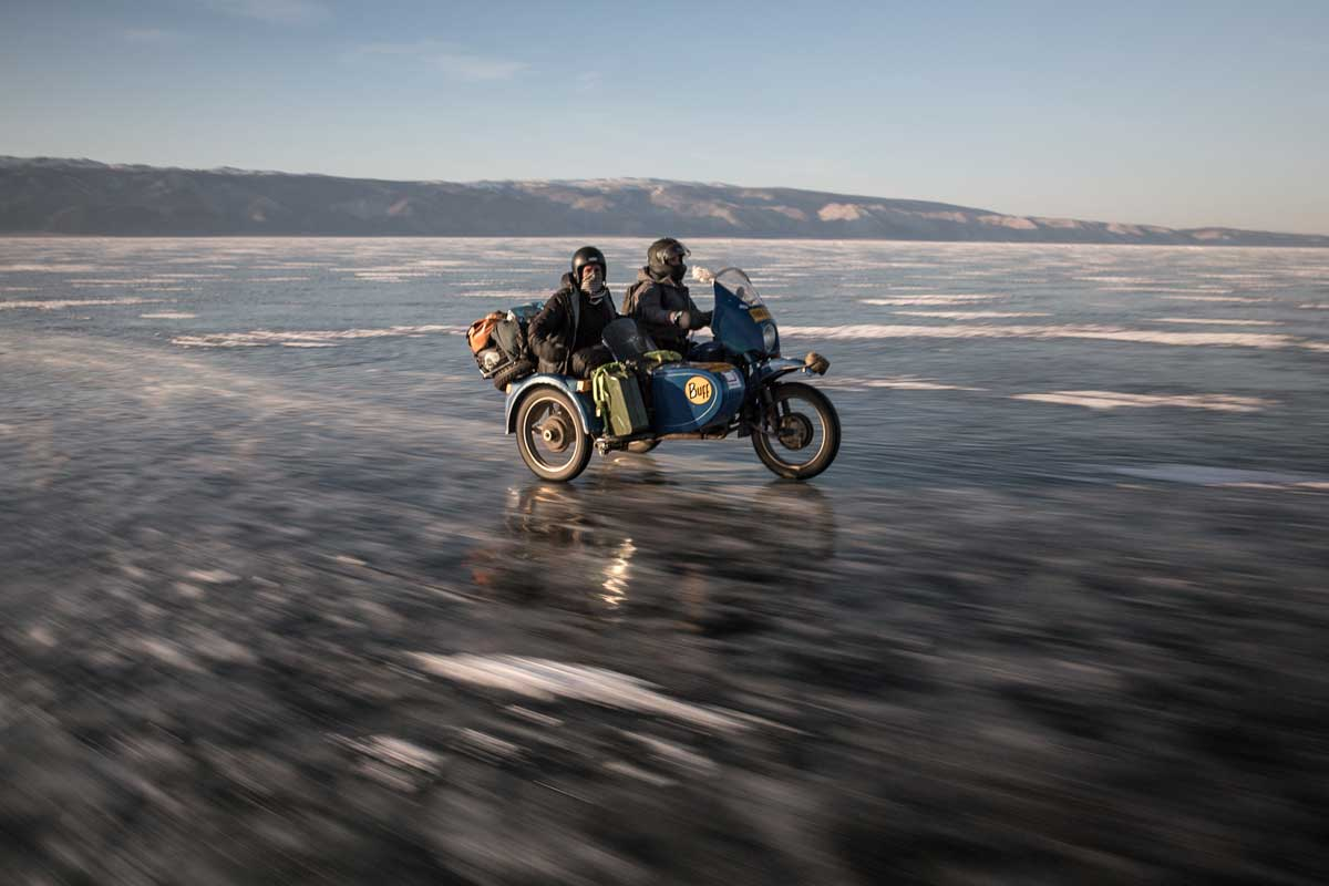 Blue sidecar and two riders and baggage traversing the icy frozen lake