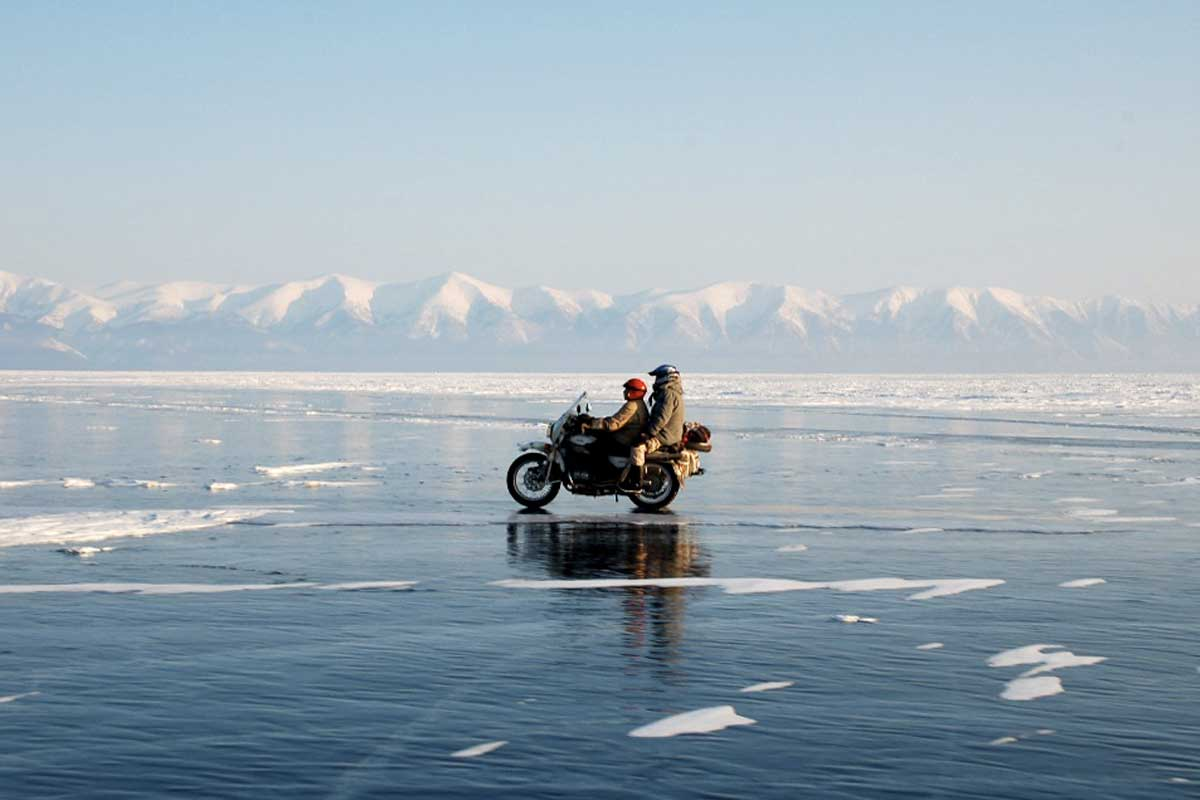 Lone bike and two riders with snowy mountains in the distance