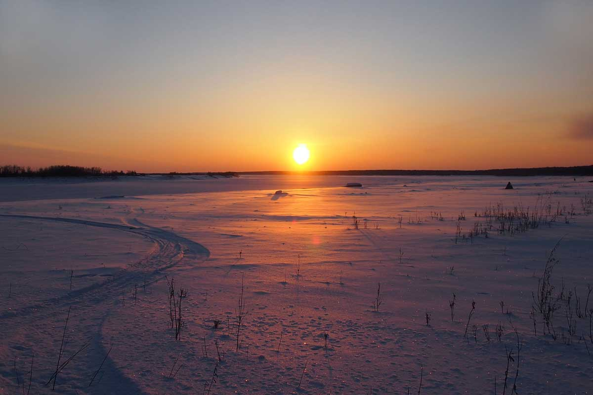 Setting sun casting an orange glow over the snowy landscape