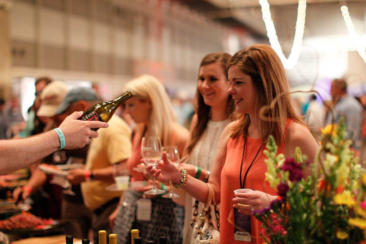 Two ladies having wine poured for them at the New Orleans Food and Wine Fest