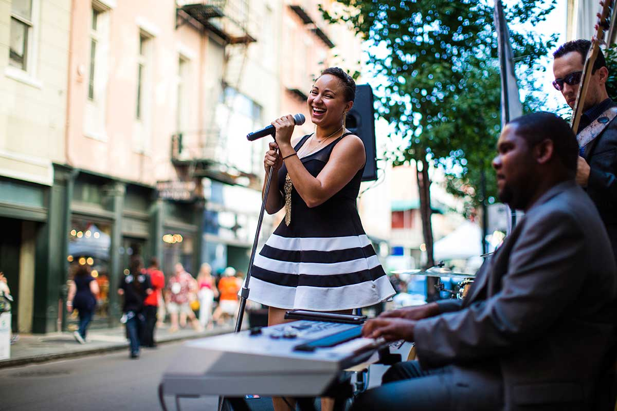 Singer in a black and white dress performing streetside