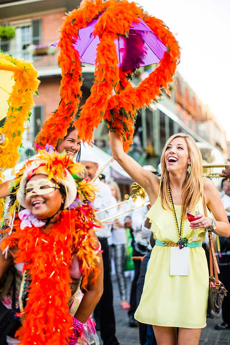 Lady in a yellow dress waving streamer in a procession, New Orleans