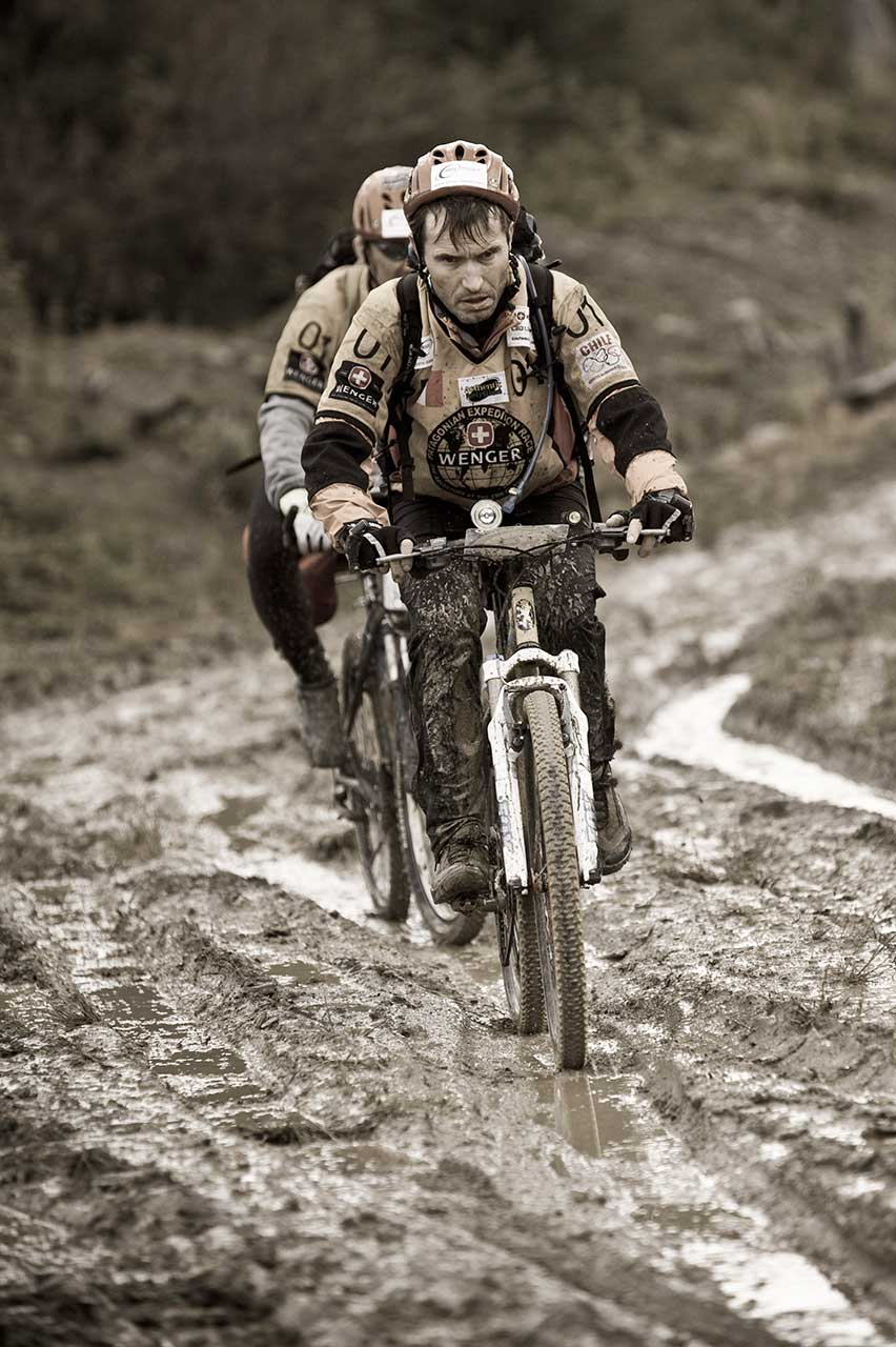 Black and white shot of two cyclists riding through a muddy road on the Patagonian Expedition Race