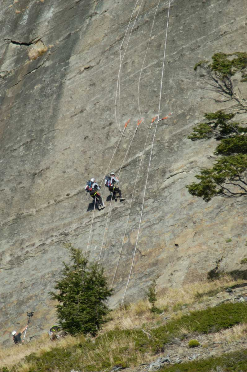 Two men scaling a sheer cliff face