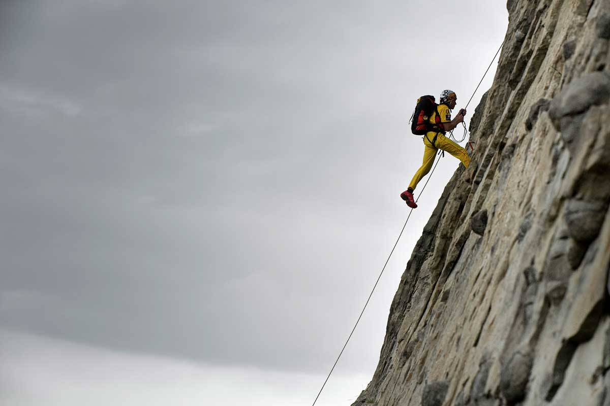Man with a backpack abseiling on a cliff face