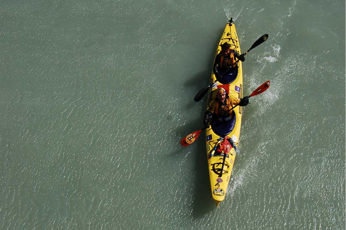 Aerial view of two canoeists in a yellow canoe paddling and looking up
