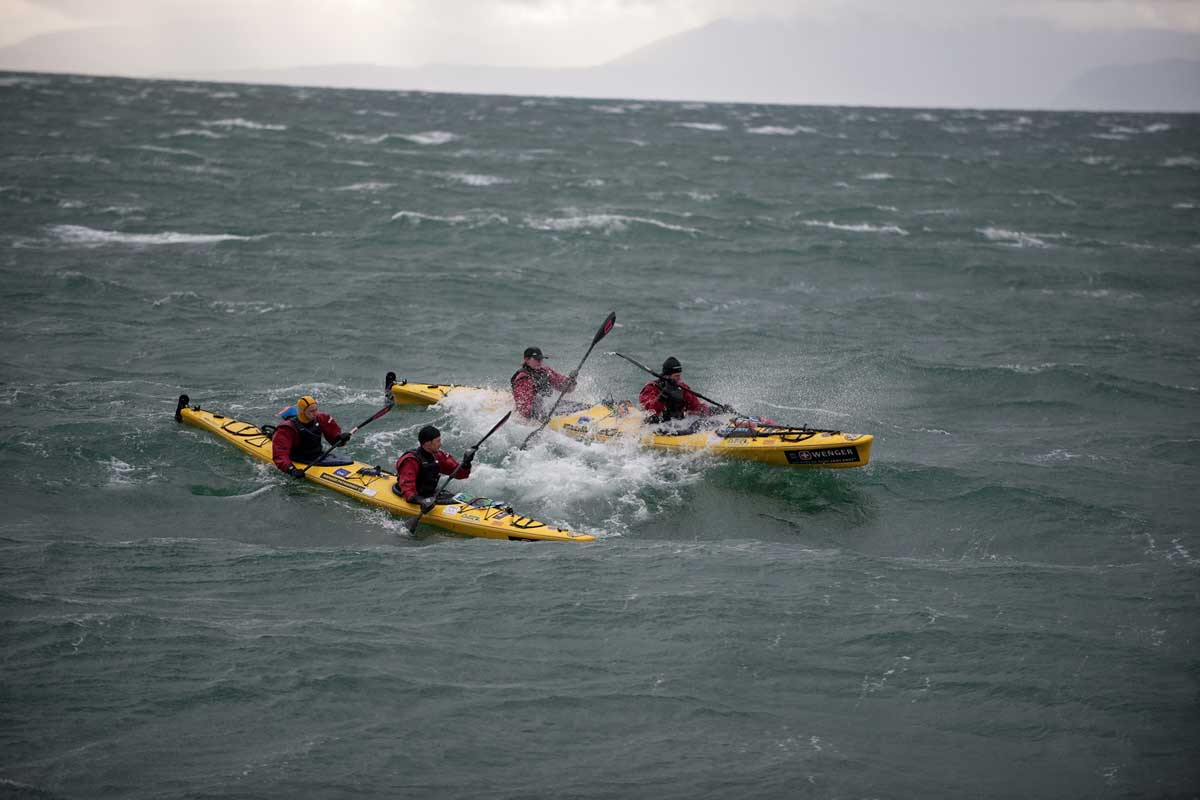 Two two-person canoes paddling through choppy water in Patagonia