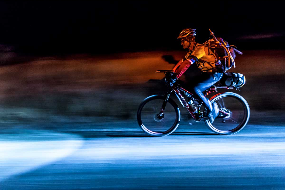 Man with a backpack cycling in the dark