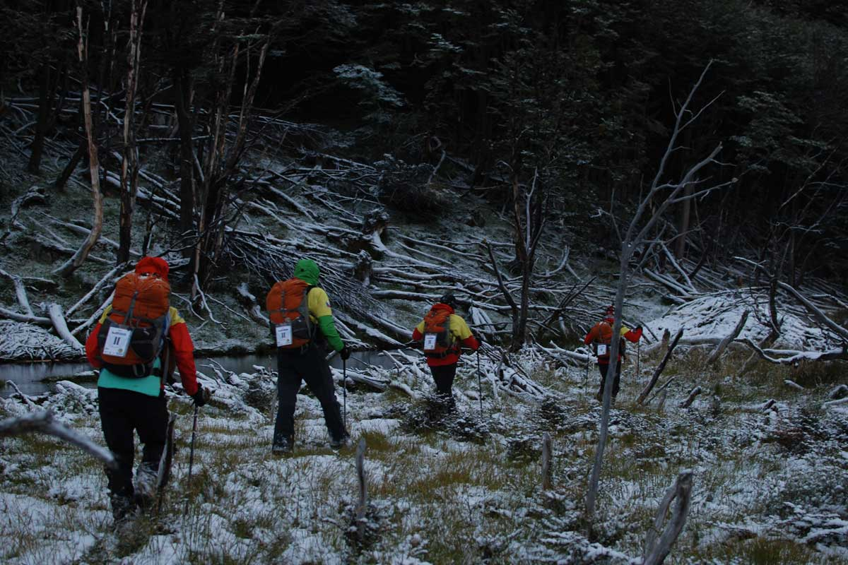 People with backpacks and trekking poles walking through snow and vegetation in dim light in Patagonia