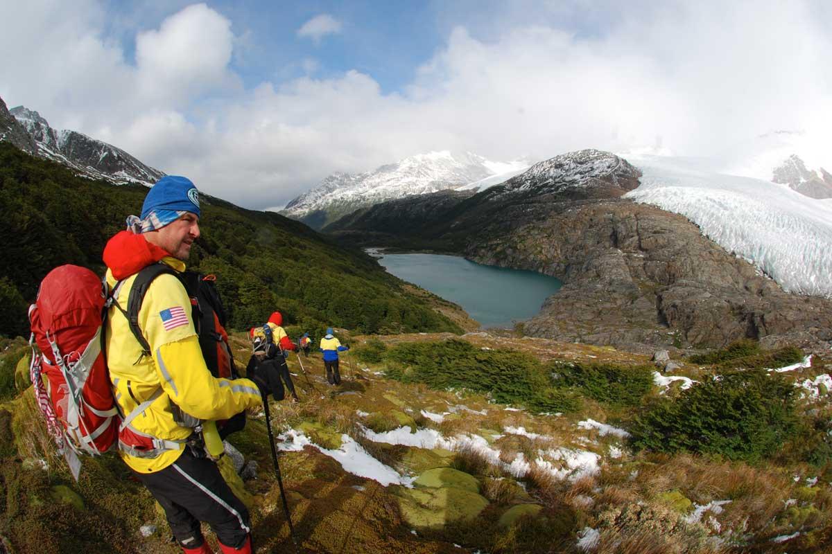 Trekkers descending a mountainside towards a lake