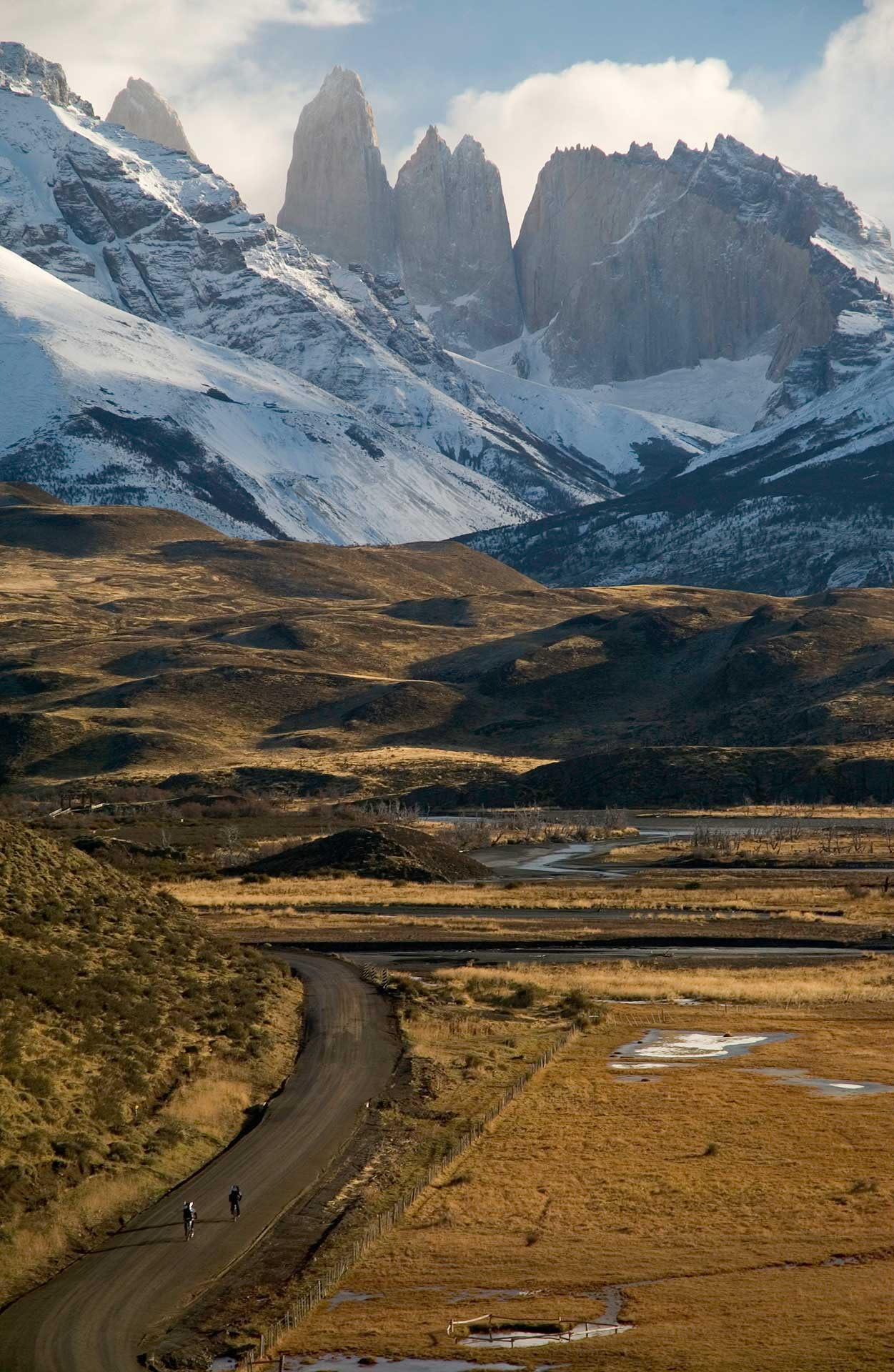 Aerial view of cyclists on a dirt road with snow covered mountains in the distance in Patagonia