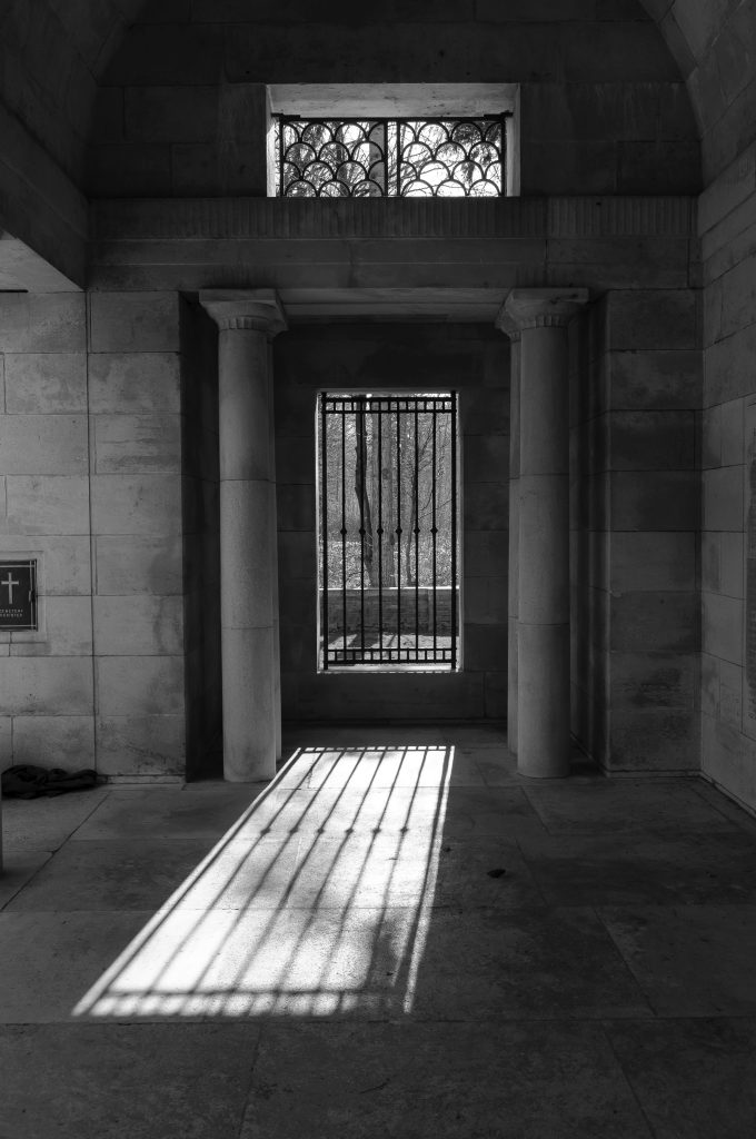An iron grill door looking out to Polygon Wood, Belgium, sunshine pouring through it making shadows on the floor