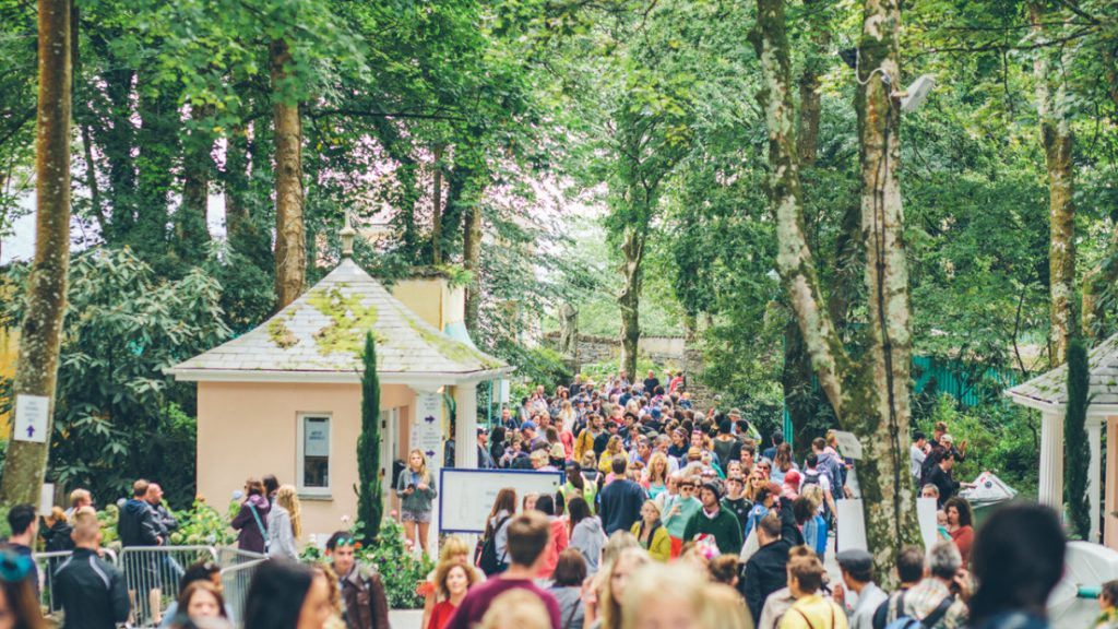 Crowd wandering through pathways between trees and houses for Festival No 6