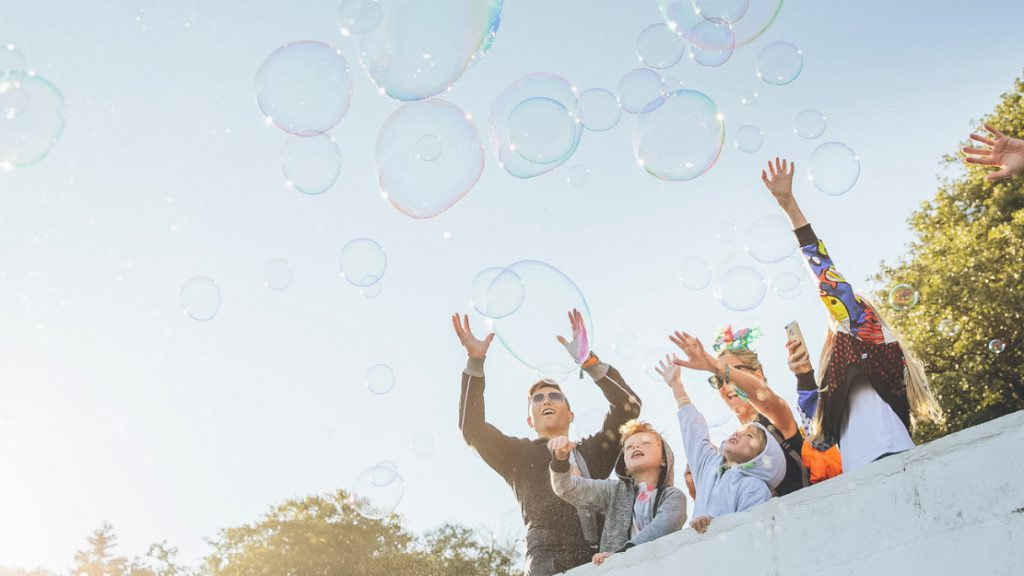 Group with arms raised to touch giant bubbles floating past