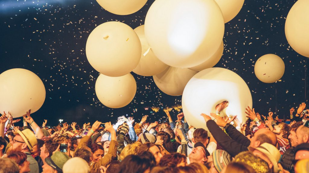 Giant white balloons float over the crowd