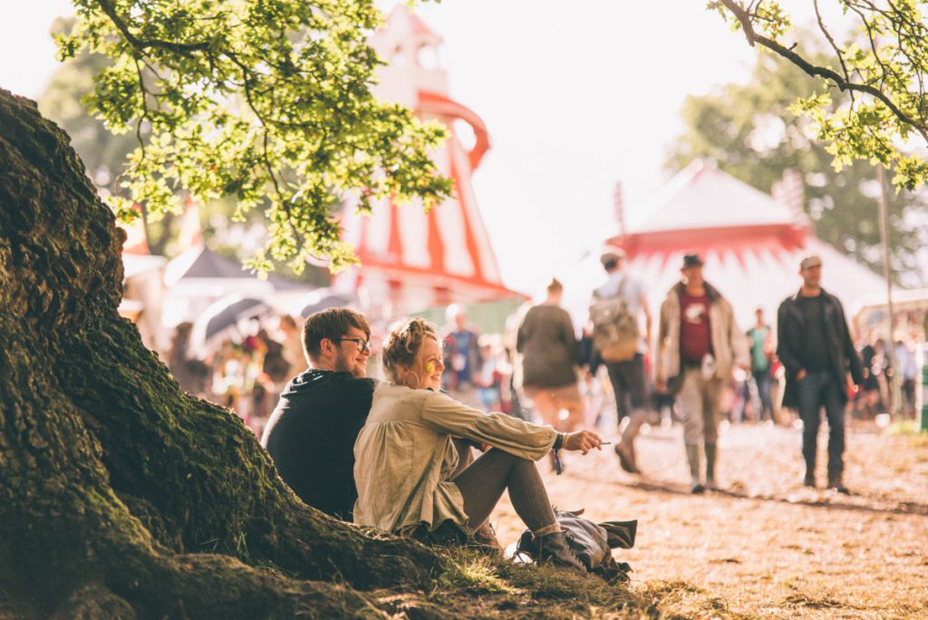 A couple sitting under a tree watching the crowd